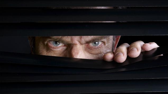 Primo piano di occhi di un uomo spia dietro le tende